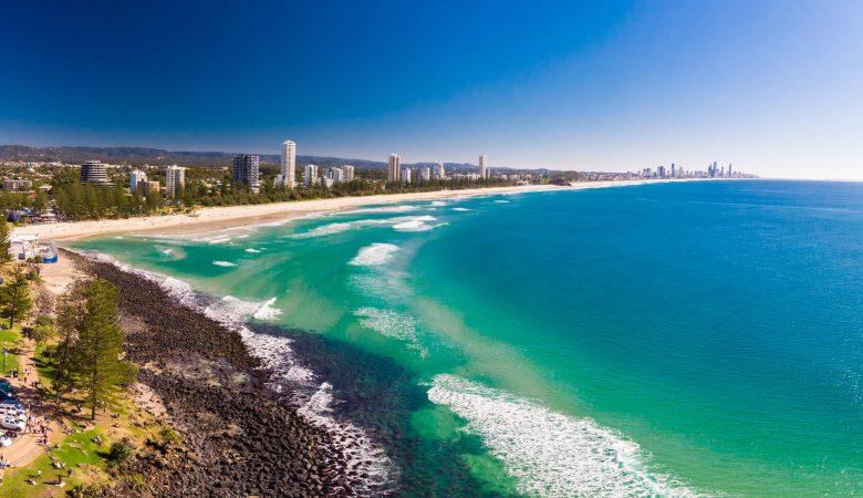 Praias da Austrália Litoral Austráliano uma praia com alguns edifícios vegetação e algumas ondas no mar